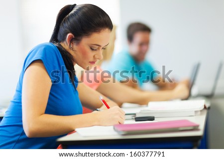 attractive female university student studying in lecture room