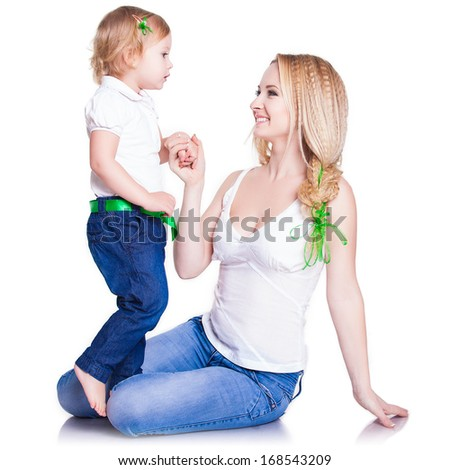 Attractive female with cute baby girl, closeup portrait of young mother and her little daughter, studio shot, happy family, child care and love concept