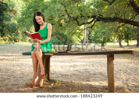 Attractive female with toothy smile reading book in the park and sitting on a wooden table beside a green apple and laptop. - stock photo