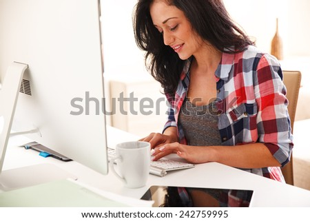 Attractive female working at home.She writing a blog in her bright living room. - stock photo