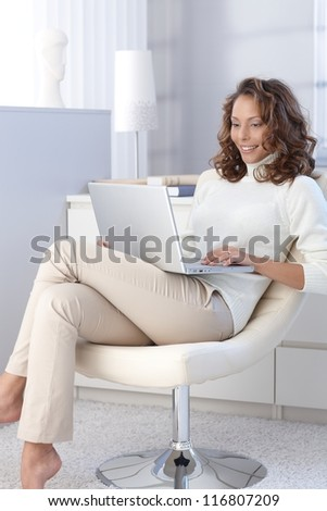 Attractive female working on laptop computer at home.