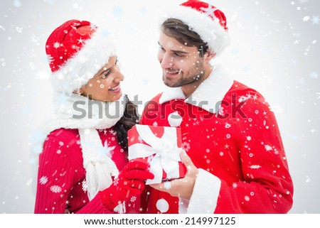Attractive festive couple holding a gift against snow falling - stock photo