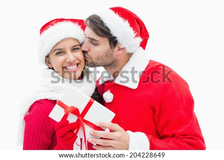 Attractive festive man giving girlfriend a kiss and present on white background