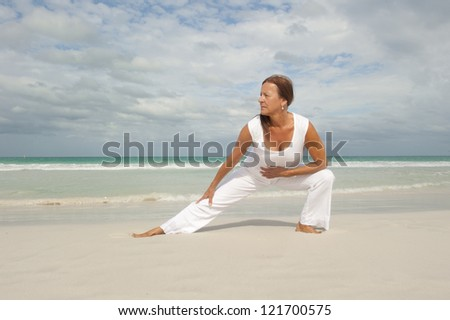 Attractive fit and healthy middle aged woman doing stretch exercising confident at beach, isolated with ocean and cloudy sky as background and copy space. - stock photo
