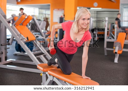 Attractive fit girl is exercising with dumbbell. She is leaning on the bench and kneeing. The lady is looking forward and smiling - stock photo