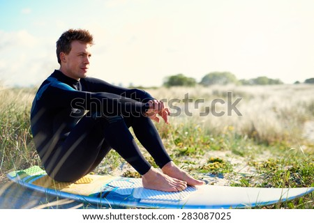 Attractive fit male surfer sitting on his surfboard on a sand-dune amongst coastal grasses staring into the distance, profile view facing right - stock photo