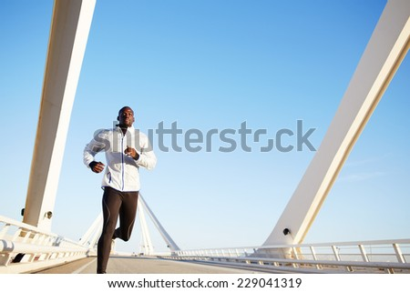 Attractive fit man running fast along big modern bridge at sunset light, black man doing workout outdoors, athletic runner in windbreaker jogging over bridge road with blue sky on background - stock photo