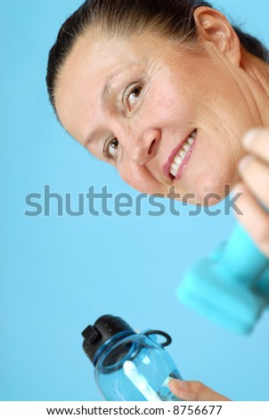 Attractive, fit older woman working out at the gym - stock photo