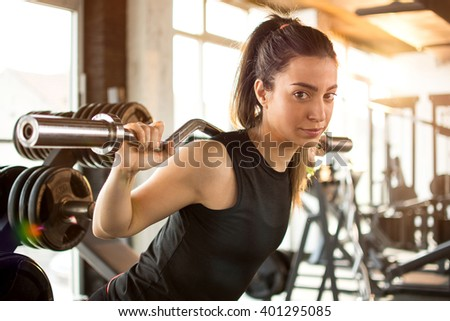 Attractive fit woman in gym exercising with weights. - stock photo