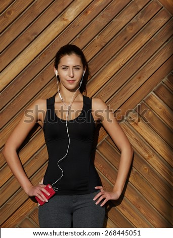 Attractive fit woman in sportswear listening to music with her headphones while training outdoors at beautiful sunny day, young female runner enjoying the sun while listen to music though earphones - stock photo