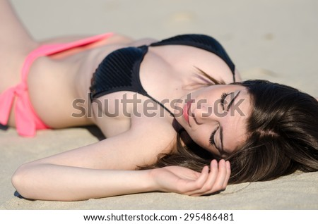 Attractive fit woman, model from Greece lying at the sand with bikini , the shoot taken from above of the head - stock photo