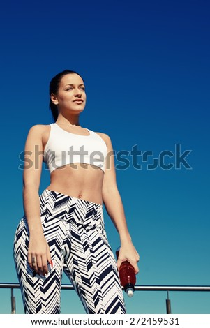 Attractive fit woman with beautiful figure standing against bright sky background, athletic female taking break after long jog by the beach holding energy drink in the hand, runner enjoying outdoors - stock photo
