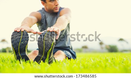 Attractive fit young man stretching before exercise, sunrise early morning backlit. Shallow depth of field, focus on shoes - stock photo