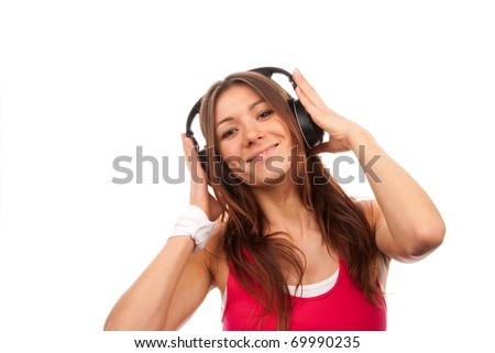 Attractive fitness brunette woman listening and enjoyingmusic in black slylish headphones, smiling, laughing and looking in camera isolated on a white background - stock photo