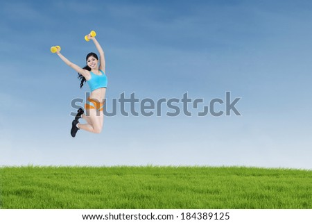 Attractive fitness woman jumping and holding dumbbells on the meadow