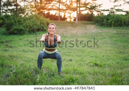 Attractive fitness woman practicing in the park on the grass. She is doing squat exercise. Sport concept