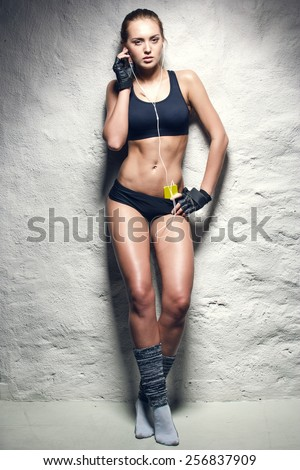 attractive fitness woman with mp3 player, caucasian brunette model - stock photo