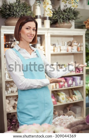 Attractive florist is standing in her store. She is raising her hands sideways and presenting her workshop proudly. The woman is smiling and looking at the camera happily - stock photo