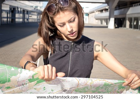 Attractive foreign female model looking on printed paper map in search of fastest directions to nearest hotel, restaurant, shopping center, main city square - stock photo