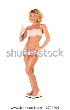 Attractive friendly blond female with athletic body in white lace underwear standing on bathroom scales, smiling and shows thumb up - stock photo