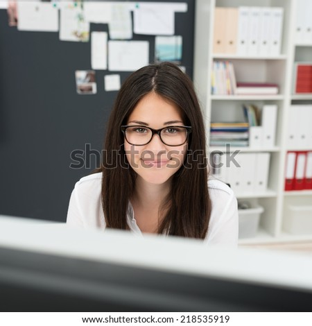 Attractive friendly businesswoman wearing glasses working at her desk looking over the top of her computer monitor at the camera - stock photo