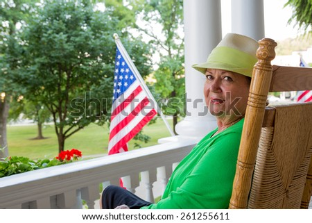 Attractive friendly trendy elderly lady in a green top and hat sitting on her patio with the American national flag flying alongside her in a patriotic gesture - happy birthday America - stock photo