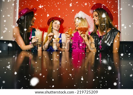 Attractive friends at a hen night drinking cocktails against snow falling - stock photo
