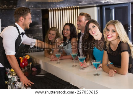 Attractive friends being served cocktails at the bar - stock photo