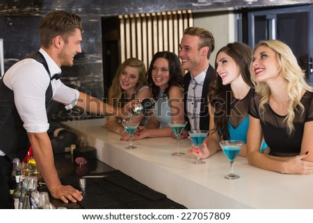 Attractive friends drinking cocktails together at the bar - stock photo