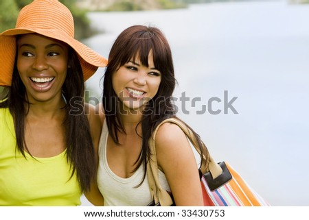 Attractive friends hanging out by the lake - stock photo