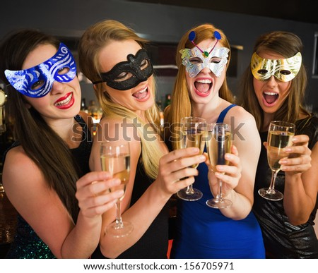 Attractive friends with masks on holding champagne glasses laughing at camera - stock photo