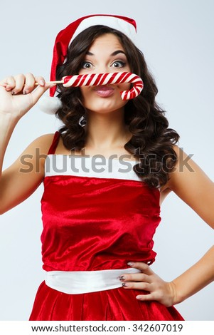 Attractive funny girl, with curly hair, wearing in red santa costume, posing with colorful candies in front of her face, on the white background, in studio, close up - stock photo