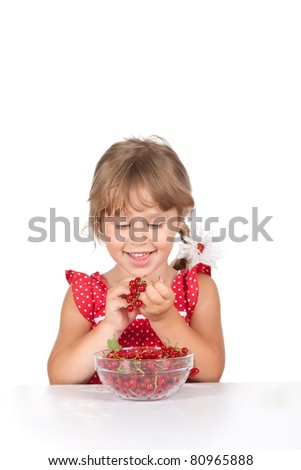 Attractive funny lovely 4 years happy little girl smile sitting at the table and eating red berry currant by hands, isolated over white background - stock photo