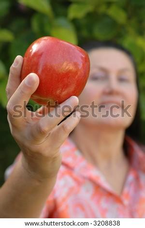 Attractive gardener holding an apple.  Healthy senior lifestyle concept. - stock photo