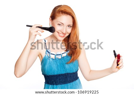 Attractive ginger Make-up artist holding brush and cosmetics on white background - stock photo
