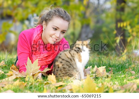 attractive girl and cat on natural background - stock photo