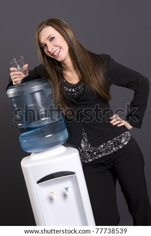 Attractive Girl at Water cooler in business office break time - stock photo