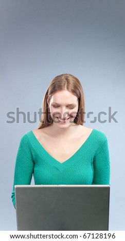 Attractive girl browsing internet, wearing green sweater, smiling - stock photo