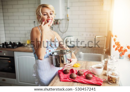 Attractive girl cooking on her kitchen. Retro style. Fashion.