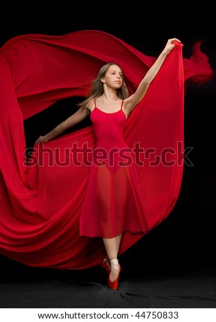 Attractive girl dancer dances in a red dress.