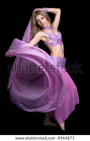 Attractive girl dances east dance isolated on a black background - stock photo