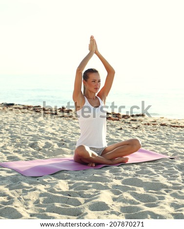 attractive girl doing yoga on the beach. - stock photo