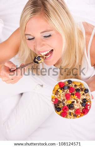 Attractive girl eating healthy bowl of cereals. Shot from upper view. Focused on eyes
