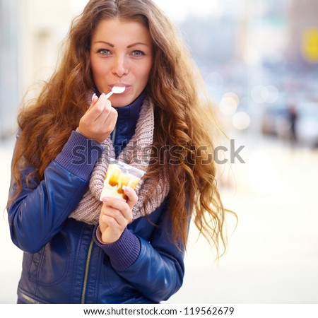 attractive girl eating ice cream on the city street - stock photo