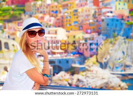 Attractive girl enjoying travel to Europe, standing on wonderful colorful buildings background, famous street in Cinque Terre - stock photo