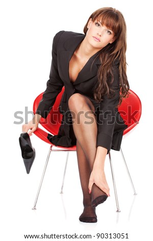 Attractive girl give herself foot massage and looking in camera, isolated on white background - stock photo