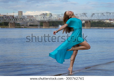 Attractive girl have fun at the urban beach in the water. Woman portrait with blue dress. - stock photo