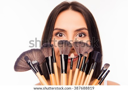 Attractive girl hiding behind makeup brushes, close up photo - stock photo