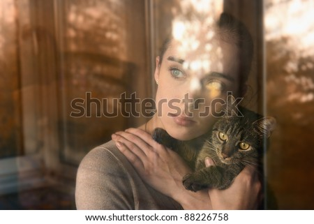 attractive girl holding a cat and sits by the window - stock photo