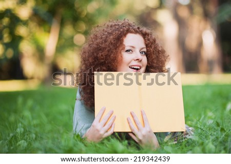 Attractive girl holding an open book outdoor